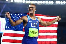 2016 Rio Olympics - Athletics - Final - Men's Decathlon 1500m - Olympic Stadium - Rio de Janeiro, Brazil - 18/08/2016. Ashton Eaton (USA) of USA smiles while wearing the national flag. REUTERS/Lucy Nicholson