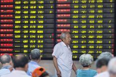 Un inversor camina junto a una pantalla que muestra información bursátil en una correduría en Nanjing. 27 de julio de 2016. El índice chino CSI300 borró unas pérdidas iniciales el viernes y cerró estable, y anotó una ganancia de un 2,1 por ciento en la semana. China Daily/via REUTERS  IMAGEN SOLO PARA USO EDITORIAL