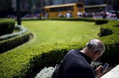 Una persona revisando su teléfono móvil en Ciudad de México, oct 8, 2015. El regulador del sector de telecomunicaciones de México decidió posponer un año la licitación de la banda de radiofrecuencias de 2.5 Gigahertz (GHz), que servirá principalmente para prestar servicios móviles de internet de banda ancha.  REUTERS/Edgard Garrido