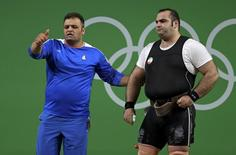 2016 Rio Olympics - Weightlifting - Final - Men's +105kg - Riocentro - Pavilion 2 - Rio de Janeiro, Brazil - 16/08/2016. Behdad Salimikordasiabi (IRI) of Iran and his coach react. REUTERS/Damir Sagolj