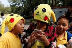 "Children wearing hats of a Pokemon character, Pikachu, play Pokemon Go during a gathering to celebrate ""Pokemon Day"" in Mexico City, Mexico August 21, 2016.  REUTERS/Carlos Jasso"