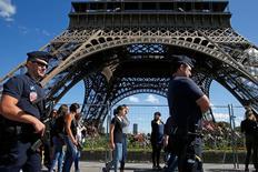 Los ataques islamistas han alejado a miles de turistas de París y de sus principales atracciones, lo que ha hecho perder a la región unos 750 millones de euros en ingresos, dijeron responsables el martes. En la imagen, policías franceses patrullan junto a turistas en la Torre Eiffel de París, el 20 de agosto de 2016. REUTERS/Pascal Rossignol