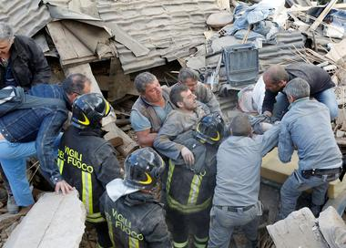 A man is carried away after having been rescued alive from the ruins...