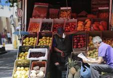 Un vendedor de frutas espera por clientes junto a un hombre que lee el diario, en una calle en Ciudad de México, México. 13 de agosto de 2014. La inflación interanual de México se aceleró a un 2.80 por ciento hasta la primera mitad de agosto, su mayor nivel en cinco meses, aunque todavía se ubica dentro del objetivo del banco central, mostraron el miércoles cifras oficiales. REUTERS/Henry Romero