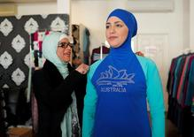 Aheda Zanetti (L), designer of the Burkini swimsuit, adjusts one of the swimsuits on model Salwa Elrashid at her fashion store in Sydney, August 23, 2016.   REUTERS/Jason Reed