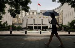 Una mujer camina cerca de la sede del Banco Central de China, en Pekín. 21 de junio de 2013. El banco central de China instó a los prestamistas del país a que extiendan los plazos de sus créditos, lo que sugiere un descontento con una tendencia reciente centrada en los préstamos a un día, dijeron el jueves fuentes bancarias a Reuters.REUTERS/Jason Lee/File Photo