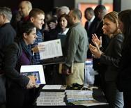 Una representante ed la firma Hogan Lovells habla con una persona durante una feria de trabajos en Washington. 9 de abril de 2014. El número de estadounidenses que pidieron el subsidio por desempleo cayó inesperadamente la semana pasada, lo que sugirió que el mercado laboral continúa ganando impulso. REUTERS/Gary Cameron