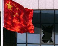 """Флаг Китая у разбитого окна китайского посольства в Белграде. 8 мая 1999 года. Взрыв автомобиля у здания китайского посольства в Киргизии во вторник был """"атакой смертника"""", сообщило китайское госинформагентство Синьхуа со ссылкой на представителя службы безопасности Киргизии. REUTERS/Petar Kujundzic"""