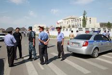 Следователи и милиционеры у места взрыва бомбы рядом с посольством Китая в Бишкеке 30 августа 2016 года. Президент Киргизии приказал усилить меры безопасности в столице и взять под усиленную охрану иностранные дипмиссии после того, как утром во вторник смертник на автомобиле протаранил ворота китайского посольства. REUTERS/Vladimir Pirogov