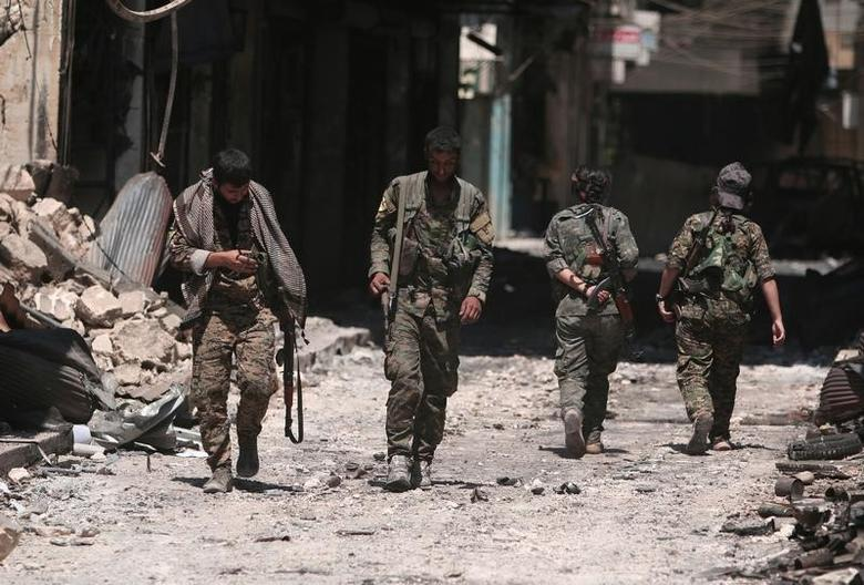 Syria Democratic Forces (SDF) fighters walk on the rubble of damaged shops and buildings in the city of Manbij, in Aleppo Governorate, Syria, August 10, 2016. REUTERS/Rodi Said