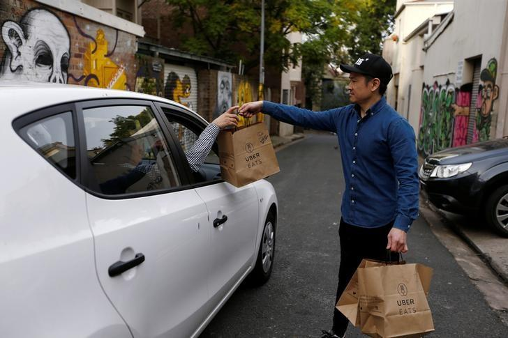 An Uber driver takes delivery of bags of donuts destined for a customer via Uber Eats in Sydney, August 12, 2016. Picture taken August 12, 2016. REUTERS/Jason Reed