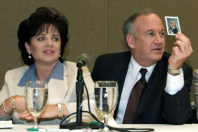 Patsy Ramsey looks down as her husband John Ramsey (R) produces a picture of their daughter Jon-Benet Ramsey during a press conference where they released the results of an independent lie detector test, in Atlanta, Georgia, U.S. May 24, 2000.  Tami Chappell/File Photo