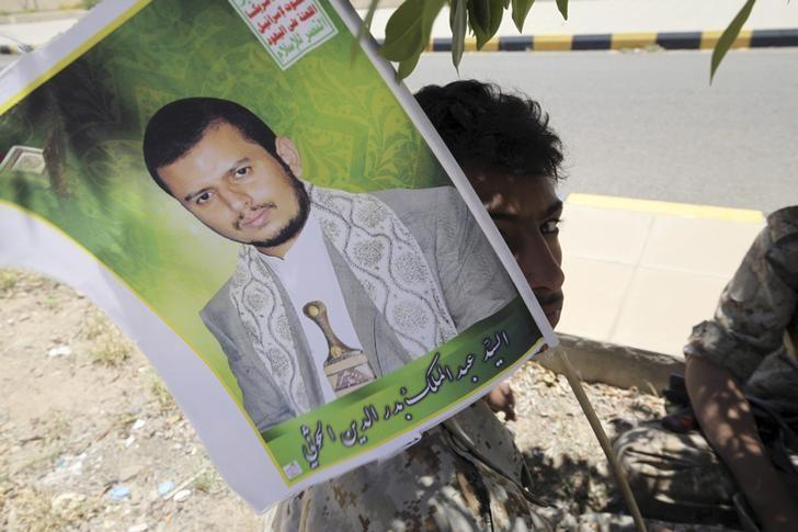 A youth dressed in military uniform holds up a poster of the Houthi movement's leader Abdel-Malek Badruddin al-Houthi as he and a friend sit under a tree after being stationed to provide security during celebrations marking the 25th anniversary of Yemen's unification, in Sanaa May 23, 2015. REUTERS/Mohamed al-Sayaghi/Files
