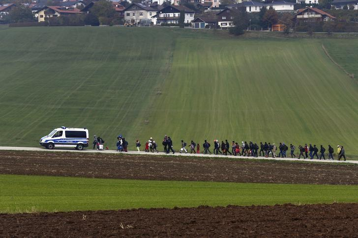 Immigrants are escorted by German police to a registration centre, after crossing the Austrian-German border in Wegscheid near Passau, Germany, October 20, 2015. REUTERS/Michael Dalder/Files