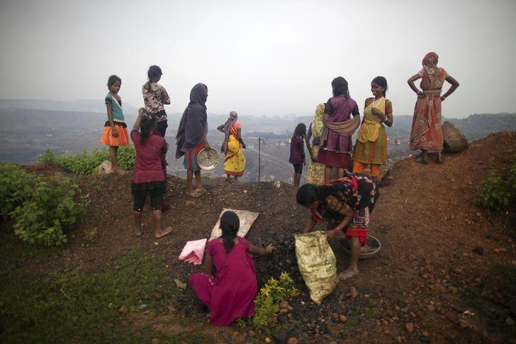 Local women stand atop of an open cast coal field as other collect coal at Dhanbad, Jharkhand September 20, 2012.  REUTERS/Ahmad Masood/Files