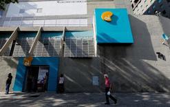 Personas caminan frente a la sede del grupo de telecomunicaciones Oi, en Río de Janeiro, Brasil. 22 de junio de 2016. Las crecientes tensiones en el proceso de bancarrota de la brasileña Oi han llevado a algunos tenedores de bonos a considerar al gobierno de Brasil como un posible aliado, frente a inversores a quienes consideran una amenaza para la supervivencia de la mayor compañía de telefonía del país. REUTERS/Sergio Moraes