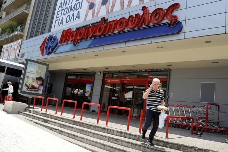 A man holding a shopping bag exits a Marinopoulos supermarket, while the Greek retail group Marinopoulos applies for creditor protection, in Athens, Greece,  June 29, 2016. REUTERS/Michalis Karagiannis