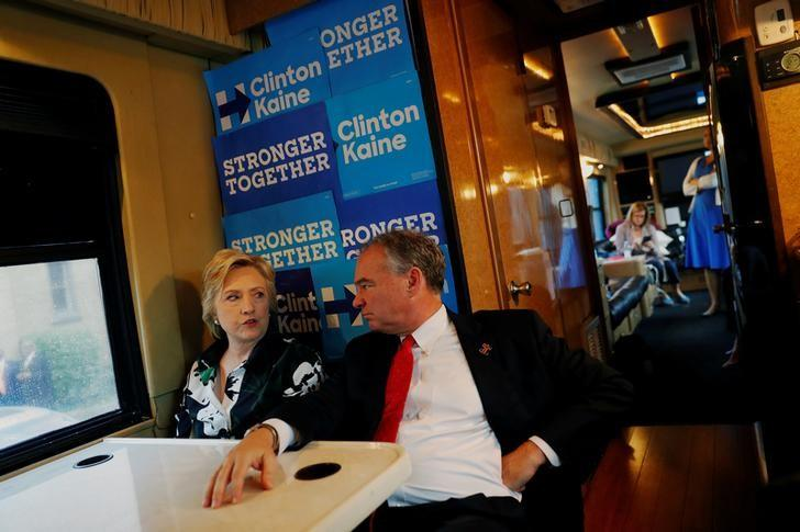 Democratic presidential nominee Hillary Clinton speaks with vice presidential nominee Tim Kaine (D-VA) aboard their bus outside Imani Temple Ministries in Cleveland, Ohio, U.S. July 31, 2016. REUTERS/Aaron P. Bernstein/Files