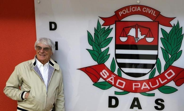 Formula One chief Bernie Ecclestone poses next to a police logo at police central station in Sao Paulo, Brazil, August 8, 2016.  REUTERS/Paulo Whitaker