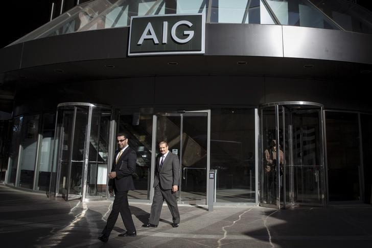 People exit the AIG building in New York's financial district March 19, 2015. REUTERS/Brendan McDermid