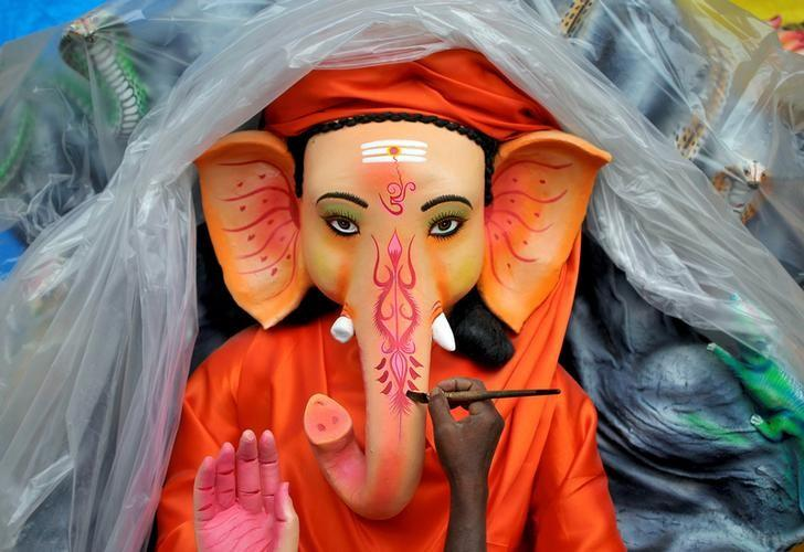 An artisan paints an idol of Hindu god Ganesh, the deity of prosperity, at a workshop ahead of the Ganesh Chaturthi festival, in Bengaluru, India August 30, 2016. REUTERS/Abhishek N. Chinappa/Files