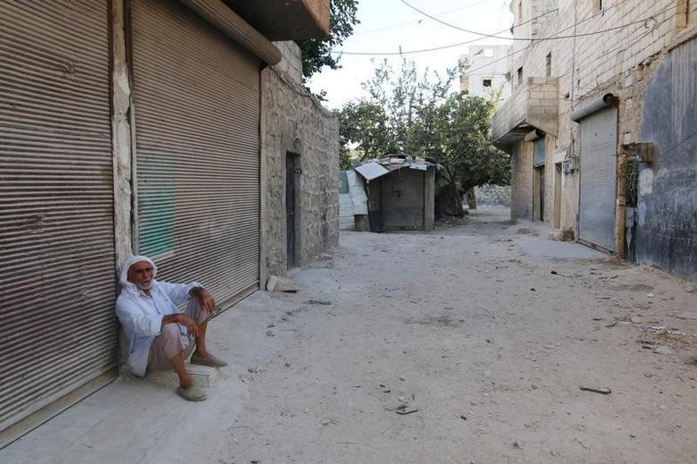 A man sits in front of closed shops in the rebel-held al-Sheikh Said neighbourhood of Aleppo, Syria September 1, 2016. REUTERS/Abdalrhman Ismail