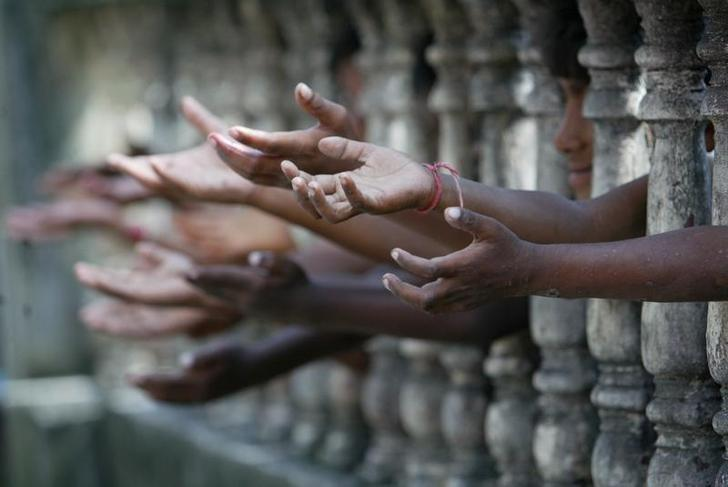 Homeless children reach out from behind a fence as they wait to collect free clothes at a local charity in Siliguri September 27, 2006. REUTERS/Rupak De Chowdhuri/Files