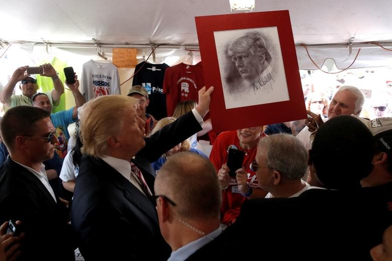 Republican presidential nominee Donald Trump holds up a drawing of him during a campaign stop at the Canfield County Fair in Canfield, Ohio, U.S., September 5, 2016.  REUTERS/Mike Segar