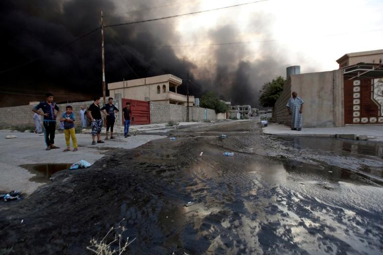 Residents look at oil spill from wells, set ablaze by Islamic State militants before fleeing the oil-producing region of Qayyara, in Qayyara, Iraq, August 29, 2016. REUTERS/Azad Lashkari