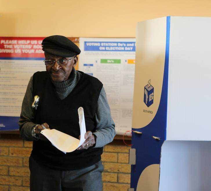 Archbishop Emeritus Desmond Tutu holds his balot paper before he casts his vote during the local government elections in Milnerton, Cape Town, South Africa. August 3, 2016. Reuters/Sumaya Hisham