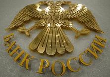 Герб Банка России в его здании в Москве 13 марта 2015 года. Банк России в августе аккредитовал первое российское рейтинговое агентство АКРА, которое через полтора - два месяца собирается начать активно присваивать рейтинги, и подтвердил намерения отказаться в нормативных документах от привязки к иностранным рейтингам в пользу российских. REUTERS/Sergei Karpukhin