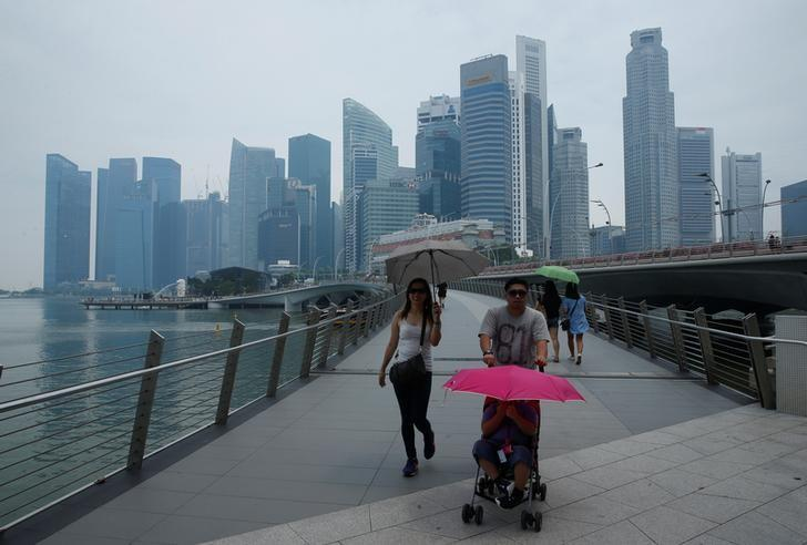 People pass skyline of Singapore's central business district shrouded by haze August 26, 2016. REUTERS/Edgar Su