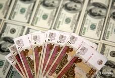 Банкноты российского рубля и доллара США. 9 марта 2015 года. Рубль удерживает плюс в среду на фоне текущей позитивной динамики нефти и подешевевшего накануне американского доллара, чьи попытки восстановиться, однако, мешают росту российской валюты. REUTERS/Dado Ruvic