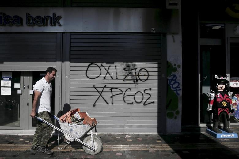 Graffiti on a closed Attica Bank branch reads ''No to the debt'' as a worker pushing a cart walks by in Athens, Greece July 13, 2015. REUTERS/Alkis Konstantinidis/File photo
