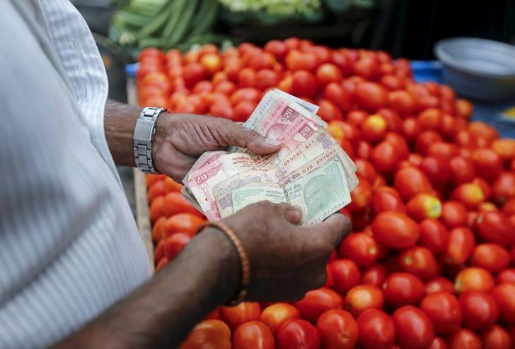 A customer counts money before paying to a vegetable vendor at a market in Mumbai, India, June 4, 2015. REUTERS/Shailesh Andrade/Files