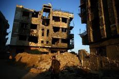 Боец сил сирийской оппозиции проходит мимо разрушенного войной здания в пригороде Дамаска 6 сентября 2016. Оппозиция отвергнет любое соглашение России и США о судьбе Сирии, если таковое будет разительно отличаться от её собственного плана перехода власти в охваченной гражданской войной стране, сказал главный координатор делегации на переговорах. REUTERS/Bassam Khabieh
