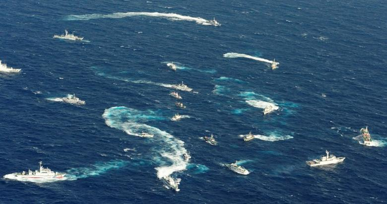 An aerial view shows Japan Coast Guard patrol ship, fishing boats from Taiwan and Taiwan's Coast Guard vessel sailing side by side near the disputed islands in the East China Sea, known as Senkaku in Japan, Diaoyu in China and Tiaoyutai in Taiwan, in this photo taken by Kyodo in this file photo dated September 25, 2012.  REUTERS/Kyodo