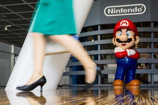 A woman walks past a figure of ''Mario'', a character in Nintendo's ''Mario Bros.'' video games, at a Nintendo centre in Tokyo July 29, 2015. REUTERS/Thomas Peter