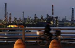 El crecimiento económico de Japón entre abril y junio fue mayor que el estimado inicialmente, dijo el jueves la Oficina del Gabinete, debido a que el gasto de capital y los inventarios fueron revisados al alza, pero una débil demanda doméstica e internacional presionaría a la expansión este trimestre. En la imagen, un hombre en bicicleta, con una fábrica al fondo en la zona industrial Keihin de Kawasaki.  REUTERS/Yuya Shino/File Photo