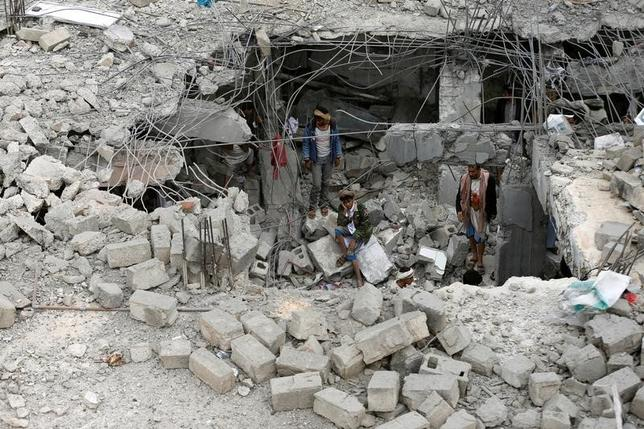 A man sits near others amidst rubble of a building destroyed by Saudi-led air strikes in the northwestern city of Amran, Yemen September 8, 2016. REUTERS/Khaled Abdullah