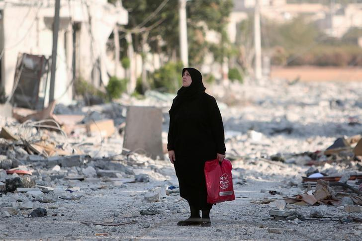 A woman stands along a damaged street in Manbij, Aleppo Governorate, Syria, August 16, 2016. REUTERS/Rodi Said/File Photo