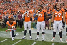 Sep 8, 2016; Denver, CO, USA; Denver Broncos inside linebacker Brandon Marshall (54) kneels during the national anthem next to defensive end Jared Crick (93) and defensive tackle Billy Winn (97) and defensive tackle Adam Gotsis (99) before the game against the Carolina Panthers at Sports Authority Field at Mile High. Mandatory Credit: Ron Chenoy-USA TODAY Sports