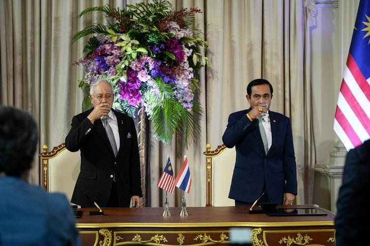 Malaysian Prime Minister Najib Razak (L) raises a glass with Thai Prime Minister Prayuth Chan-Ocha (R) at Government House in Bangkok on September 9, 2016. REUTERS/Lillian Suwanrumpha/Pool