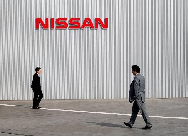 Men walk past a Nissan Motor Co logo at the company's global headquarters in Yokohama, south of Tokyo February 9, 2011.  REUTERS/Toru Hanai/File Photo