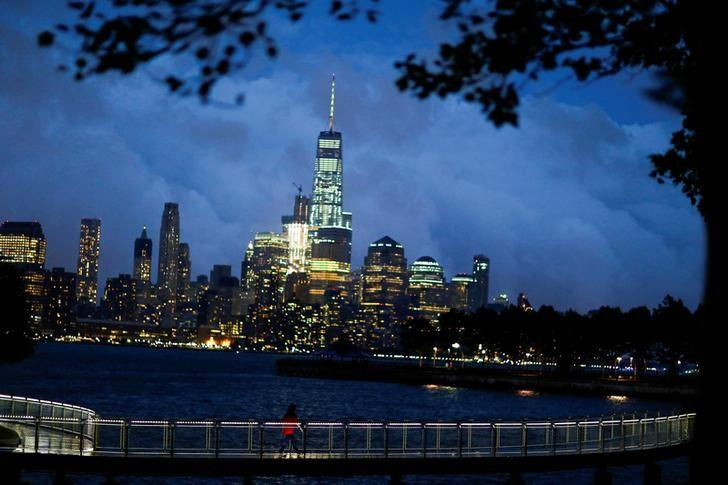 A woman walks on a bridge as low level cloud formation hovers over New York's One World Trade Center and the skyline of Lower Manhattan as seen across the Hudson River in Hoboken, New Jersey, U.S., August 21, 2016. REUTERS/Eduardo Munoz/Files