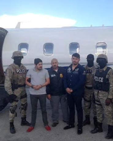 Efrain Antonio Campo Flores (2nd from L) and Franqui Fancisco Flores de Freitas stand with law enforcement officers in this November 12, 2015 photo after their arrest in Port Au Prince, Haiti.    Courtesy of U.S. Attorney's Office Manhattan/Handout via REUTERS