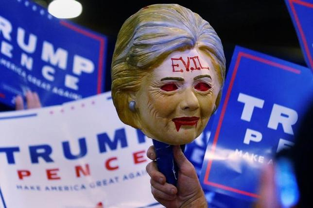 A man holds up a Hillary Clinton mask with the word Evil written across the forehead as Republican presidential nominee Donald Trump speaks at a campaign rally in Phoenix, Arizona, U.S., August 31, 2016. Picture taken August 31, 2016   REUTERS/Carlo Allegri