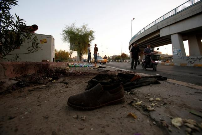 A shoe is pictured at the site of a suicide bomb attack as people look on, in the central Allawi district of Baghdad, Iraq September 11, 2016. REUTERS/Khalid al Mousily