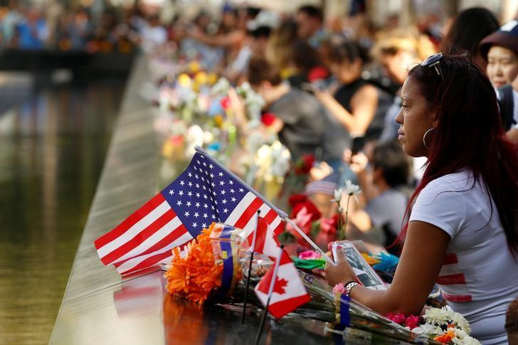 A woman holds a flag as she looks out over the National September 11 Memorial and Museum on the 15th anniversary of the 9/11 attacks in Manhattan, New York, U.S., September 11, 2016.  REUTERS/Lucas Jackson
