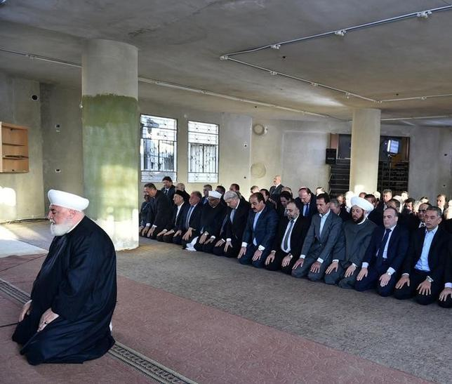 Syria's president Bashar al-Assad(4th R), prays at a mosque in a Damascus suburb of Daraya, Syria in this handout picture provided by SANA on September 12, 2016. SANA/Handout via REUTERS